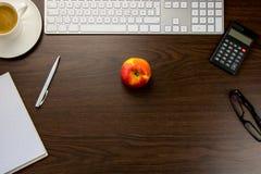 书桌在有笔记的办公室和笔,在杯子o旁边的一个键盘 免版税库存照片
