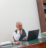 书桌的一个商人,若有所思 免版税库存图片
