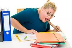书桌的不健康的女实业家吃巧克力的 免版税库存照片