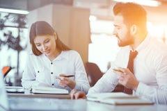 书桌的两三个同事在晴朗的办公室 免版税库存图片