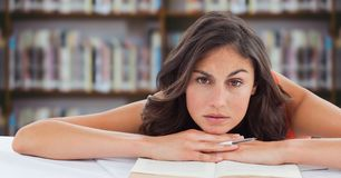 书桌的大学生反对模糊的书架 免版税库存照片