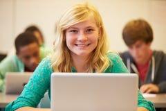 书桌的女性高中学生在使用膝上型计算机的类 库存图片