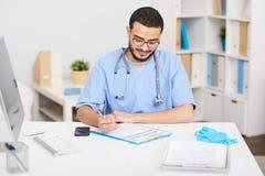 书桌的年轻中东医生Sitting 库存图片