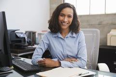 书桌的年轻女性专家微笑对照相机的 库存图片