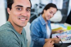 书桌的微笑的图表设计师 免版税库存图片