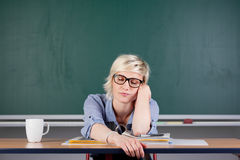 书桌的疲乏的妇女在教室 库存图片