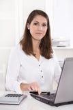 书桌的年轻微笑的女实业家在银行中 免版税库存图片