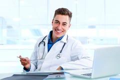 书桌的医疗男性医生有膝上型计算机和x光芒的 免版税库存照片
