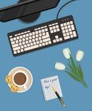 书桌背景的顶视图 有显示器、键盘、一杯咖啡用曲奇饼和在蓝色背景的白色郁金香 库存照片