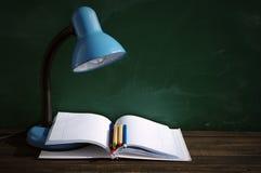 书桌蓝色灯、开放笔记本和色的铅笔反对学校绿化委员会 库存照片