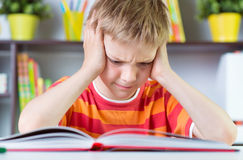 书桌读书boock的小学男孩 库存图片