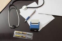 书桌医生 放置在一张黑暗的桌的听诊器、邮票和文件 免版税图库摄影