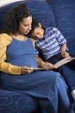 书母亲读取儿子 库存图片