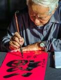 书法家老主人在红色p写着古老信件词 免版税库存照片