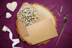 书法羽毛,在一个木圈子附近的谎言与白皮书心脏 贺卡为与地方的情人节 库存照片