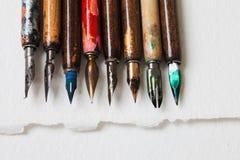 书法辅助部件,减速火箭的样式钢笔收藏 年迈的五颜六色的艺术家笔,织地不很细白皮书 免版税图库摄影