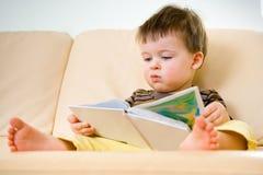 书男孩少许读取沙发 免版税库存照片