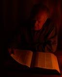 读书的一个人由烛光 免版税库存图片