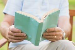 读书的一个人的中间部分在公园 免版税库存照片