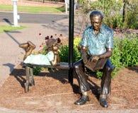 读书的一个老人的雕象对一个幼儿 免版税库存照片