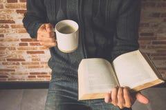 读书的一个年轻人的特写镜头,当喝咖啡从时 图库摄影