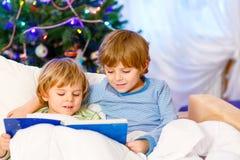 读书的两个小白肤金发的兄弟姐妹男孩在圣诞节 免版税库存图片