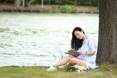 读书的中国女孩在树下 有书的白肤金发的美丽的少妇坐草 免版税图库摄影