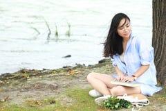 读书的中国女孩在树下 有书的白肤金发的美丽的少妇坐草 免版税库存照片