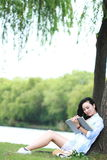 读书的中国女孩在树下 有书的白肤金发的美丽的少妇坐草 库存照片