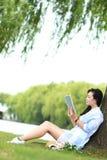 读书的中国女孩在树下 有书的白肤金发的美丽的少妇坐草 库存图片