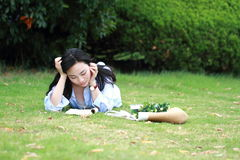 读书的中国女孩 有说谎在草的书的白肤金发的美丽的少妇 图库摄影