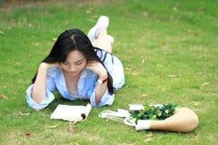 读书的中国女孩 有说谎在草的书的白肤金发的美丽的少妇 免版税库存照片