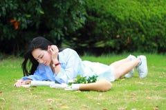 读书的中国女孩 有说谎在草的书的白肤金发的美丽的少妇 免版税库存图片