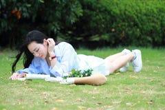 读书的中国女孩 有说谎在草的书的白肤金发的美丽的少妇 库存图片