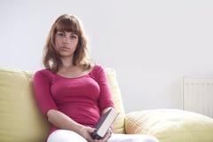 读书的女孩供以座位在黄色长沙发 免版税库存照片