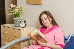 读书的女孩在上床时间 免版税图库摄影