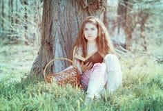 读书的女孩在树下 免版税库存照片