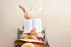 读书的女孩在海滩 免版税库存图片