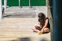 读书的女孩在船坞 免版税库存图片