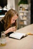 读书的女孩在餐馆 免版税库存照片