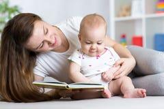 读书的女婴和母亲室内 免版税库存图片