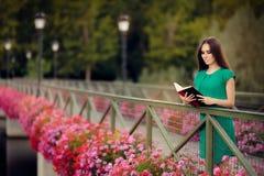 读书的妇女在有花的一座桥梁 免版税图库摄影
