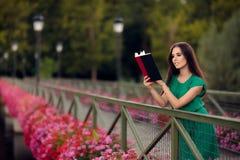 读书的妇女在有花的一座桥梁 库存照片