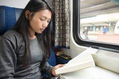 读书的妇女在火车 免版税库存照片