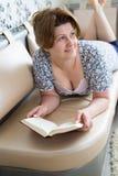 读书的妇女说谎在长沙发 库存照片