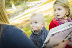 读书的妈妈对她的两个可爱的白肤金发的孩子 免版税库存图片