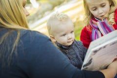 读书的妈妈对她的两个可爱的白肤金发的孩子 免版税图库摄影