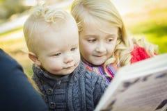 读书的学校教师对两个可爱的白肤金发的孩子 免版税库存照片