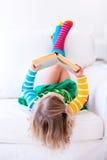 读书的小女孩在一个白色长沙发 免版税库存照片