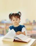 读书的小女孩在桌上 库存照片